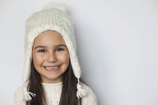 Happy smiling cute child girl in a white winter hat on white background. Positive emotiong.