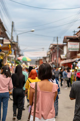 Woman on the street and blurry tourists at Walking Street Chiang Khan, Loei in Thailand.