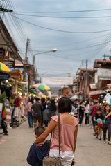 Mother and son on the street and blurry tourists at Walking Street Chiang Khan, Loei in Thailand.