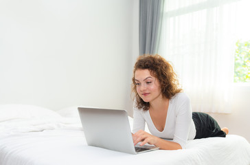 Young woman relaxing with laptop on the bed in the morning