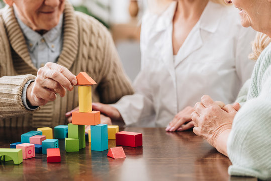 cropped view of caregiver sitting with retired man and woman and playing with wooden toys