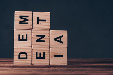 cubes with dementia letters on wooden table on black background