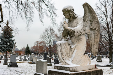 Praying Angel on top of a Tombstone at a Cemetery in Winter with Snow