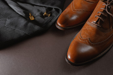Classic men's clothes such as dark suit jacket and brown leather shoes