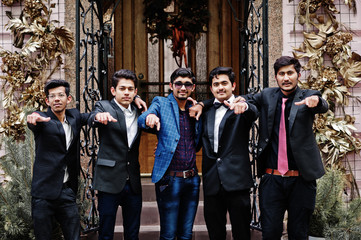 Group of 5 indian students in suits posed outdoor and show fingers.