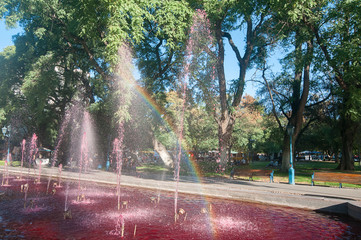 Wine fountain with rainbow. The fountains are tinted pink to look like giant pools of inviting red, Plaza de Independence of Mendoza, the city of wine, Argentina,