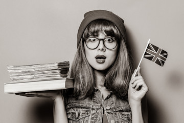 Portrait of young style hipster girl with Great Britain flag in hand and books . Image in black and...