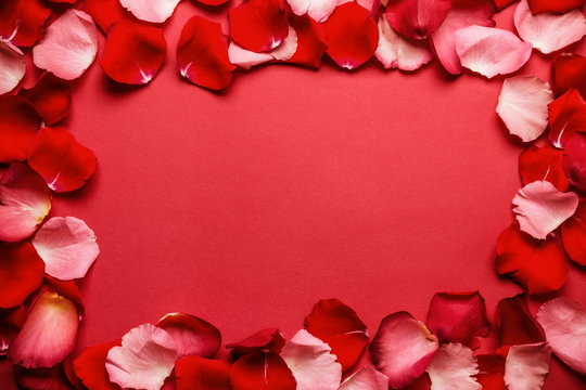 Love romantic background. Frame of rose petals on a red background