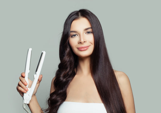 Happy woman with straight hair and curly hair using hair straightener. Cute girl straightening healthy brunette hairstyle with flat iron. Hair care concept