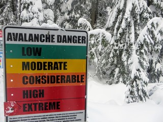 The avalanche warning sign on Cypress Mountain in Vancouver, British Columbia, Canada displays extreme level avalanche danger.  Avalanches are a serious threat.