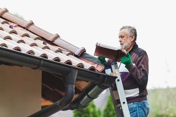 man repairs tiled roof of  house close up