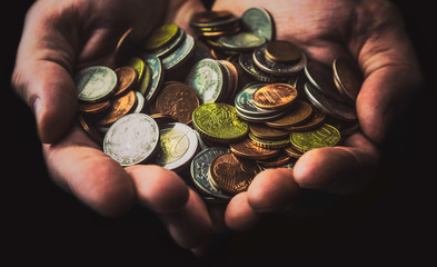 Close-up of cupped hands filled with various and colorful (silver, golden, coppery) coins isolated on a dark background. Money and finance concepts.