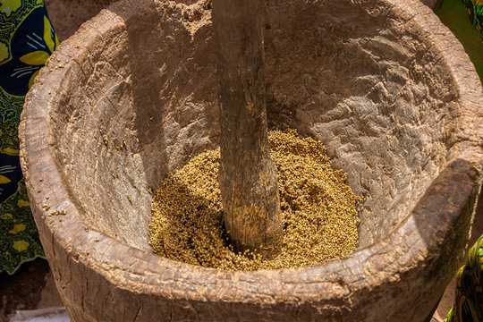 Close-up of a woman crushing cereals like millet with a wooden mortar and pestle, West Africa, Burkina Faso.