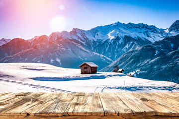 Old wooden table in the snowy mountains. Alps with a free place for an advertising product