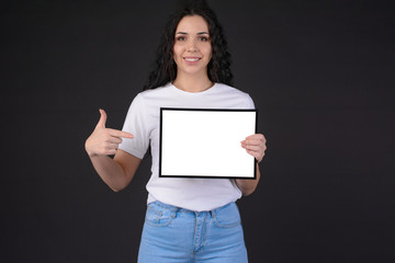 portrait of pretty young woman in white t-shirt holding empty blank photo frame with free copy space and pointing it by finger. Special offer. Hire me concept. Grateful letter