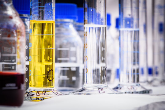 Chemistry equipment for storing chemicals, graduated cylinder filled with yellow chemical in the foreground