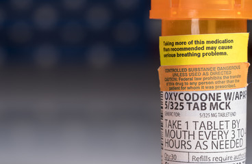 Oxycodone is the generic name for a range of opoid pain killing tablets. Prescription bottle for Oxycodone tablets and pills with USA flag in background