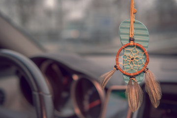 In the car hangs on the rearview mirror a decoration of flip-flops and a dream catcher. Concept: transportation or security
