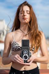 Sensual woman with retro camera on balcony