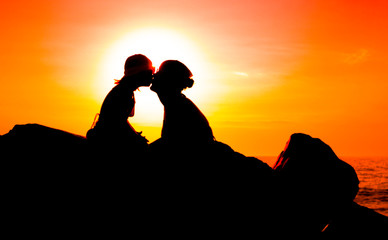 Artistic colorful style view of the silhouette of kissing mother and her young daughter on sunset sea background with copy space. Happy family, travel and vacation with children, holiday concept.