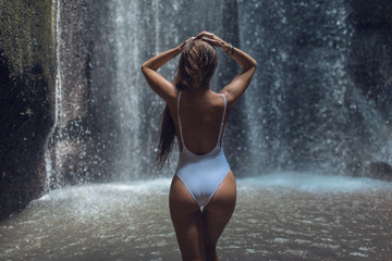 Beautiful girl in a blue swimsuit enjoys a magnificent tropical waterfall