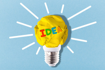 crumpled yellow paper light bulb with colorful inscription idea, inspirational image