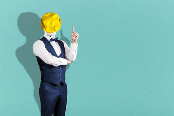 Wall Mural - a man on turquoise background in a suit with a light bulb of crumpled yellow paper instead of a head with a raised finger, the concept of the idea