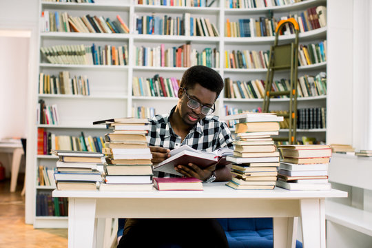 Worried African Student Looking At Books On Desk In Library