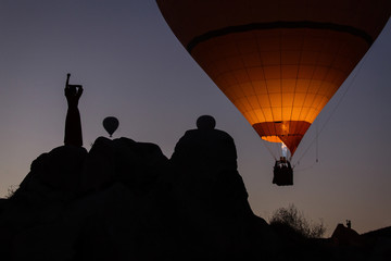 Poster Montgolfière / Dirigeable Silhouette of a woman at sunrise with hot air balloon in background
