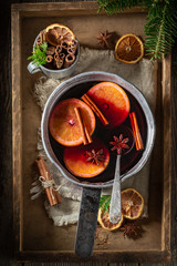 Sweet and delicious mulled red wine on rustic table