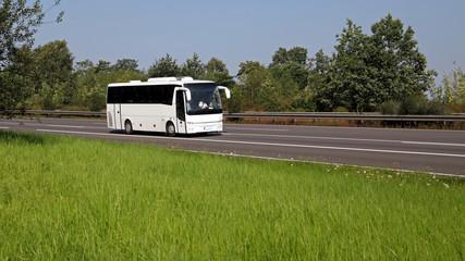 Reisebus fährt auf einer Autobahn im Sommer