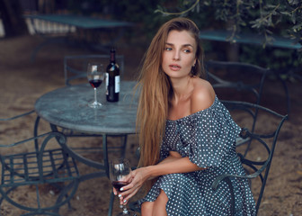 Beautiful girl with a glass of red wine is resting at a table in a beautiful garden