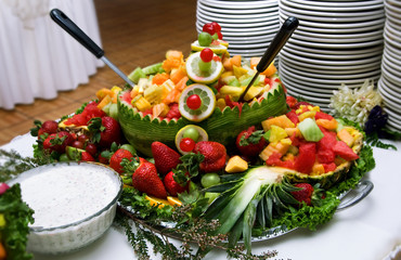 Sliced fruit, apples, oranges, strawberries, cantaloupe nicely arranged on a table