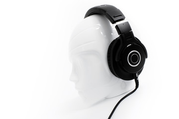 Detail on black headphones on white mannequin head with white background and soft shadows