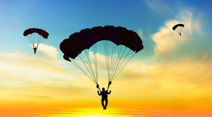 Photo sur Aluminium Aerien Silhouette parachutist landing at sunset