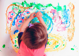Top view of little child girl painting on a white wall background. Creativity, education, child development in art, happy childhood concept.