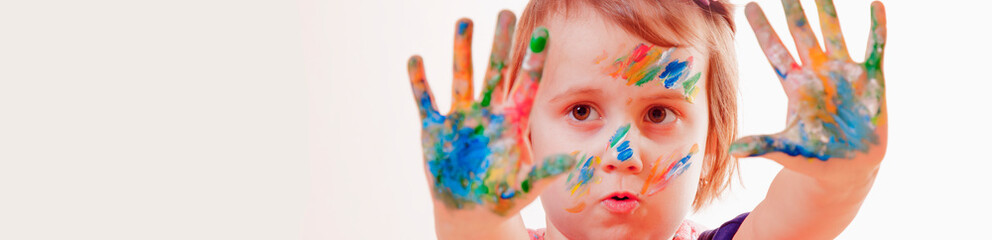 Art, creative and happiness childhood concept. Portrait of colorful painted hands and face in a beautiful little child girl.