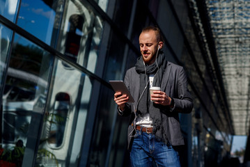 Attractive caucasian businessman wearing casual clothes walking outside, holds tablet computer and drinks coffee near modern office centre. Business concept.