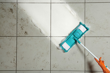 Woman cleaning tile floor with mop, top view. Space for text