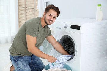 Young man using washing machine at home. Laundry day