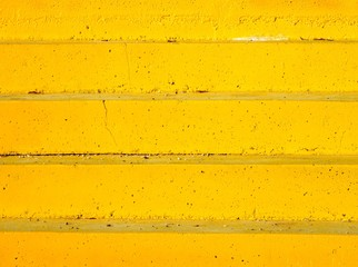 Rough textured yellow concrete staircase under bright sunlight