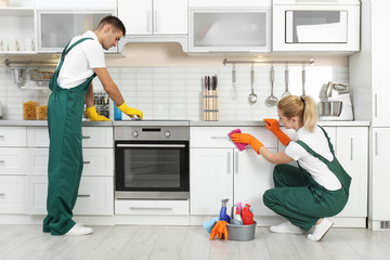 Team of janitors cleaning kitchen in house