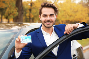 Young man holding driving license near open car