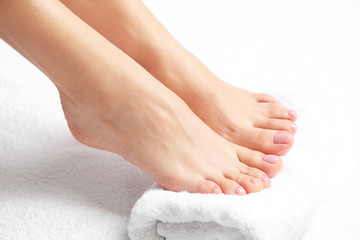 Woman with smooth feet on white towel, closeup. Spa treatment