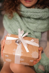Girl holding a box with a gift in their hands. New Year's and Christmas.