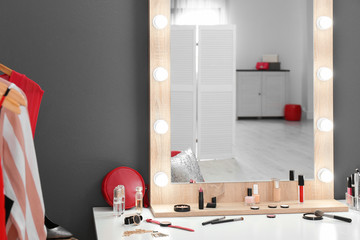 Table with makeup products and mirror near grey wall. Dressing room