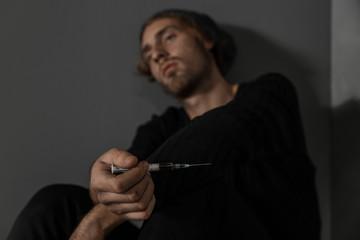 Young drug addict with syringe sitting near grey wall