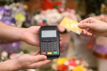 Woman using credit card for terminal payment in floral shop, closeup