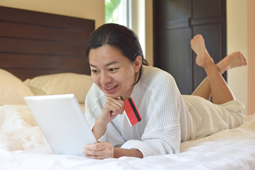 Relax women shopping online with credit card and tablet on the bed at home