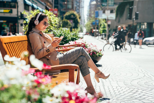 asian woman listening to music resting on bench